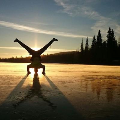 Kuva auringonlaskun edessä olevasta käsillä seisojasta